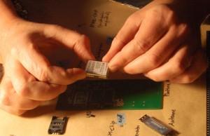 Ein Bauteil wird auf der Platine platziert. In einer Fabrik machen das Maschinen.